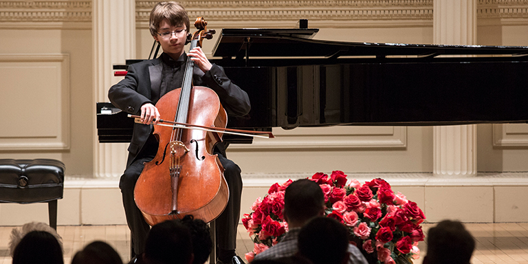 Andrew Bailey playing his cello in front of a grand piano in an ornate hall. Audience and roses in the foreground.
